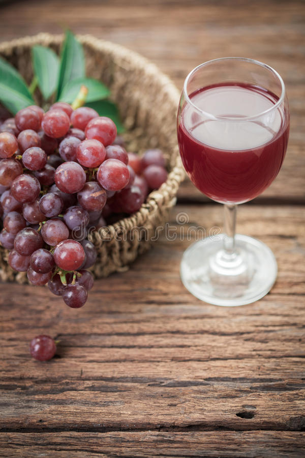 Glass of wine or grape juice and fruit on wooden table royalty free stock photo