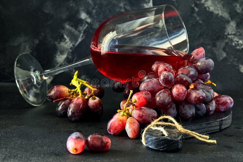 Glass of wine with grapes on a black wooden stand royalty free stock photos