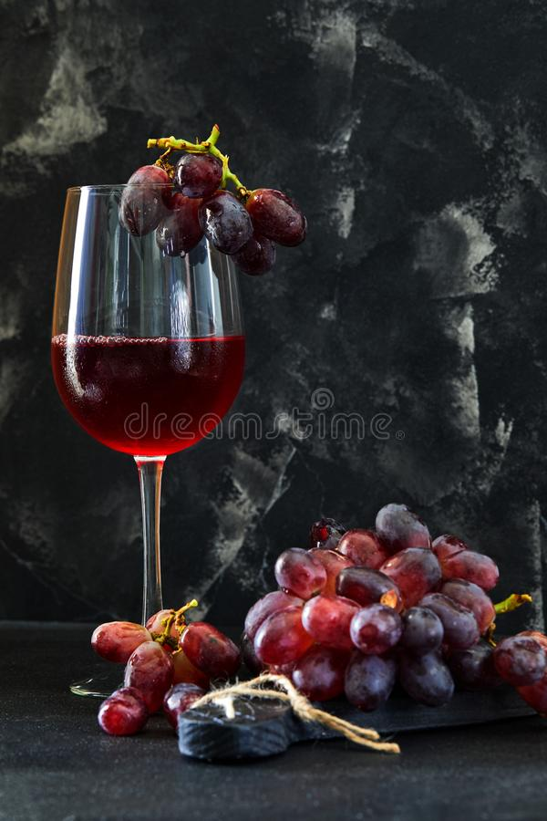 Glass of wine with grapes on a black wooden stand stock images