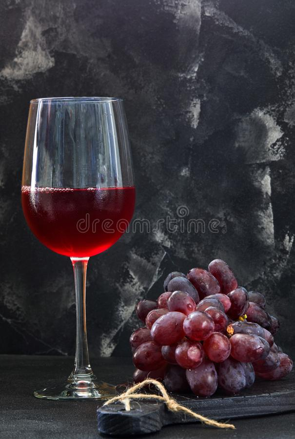 Glass of wine with grapes on a black wooden stand stock photo