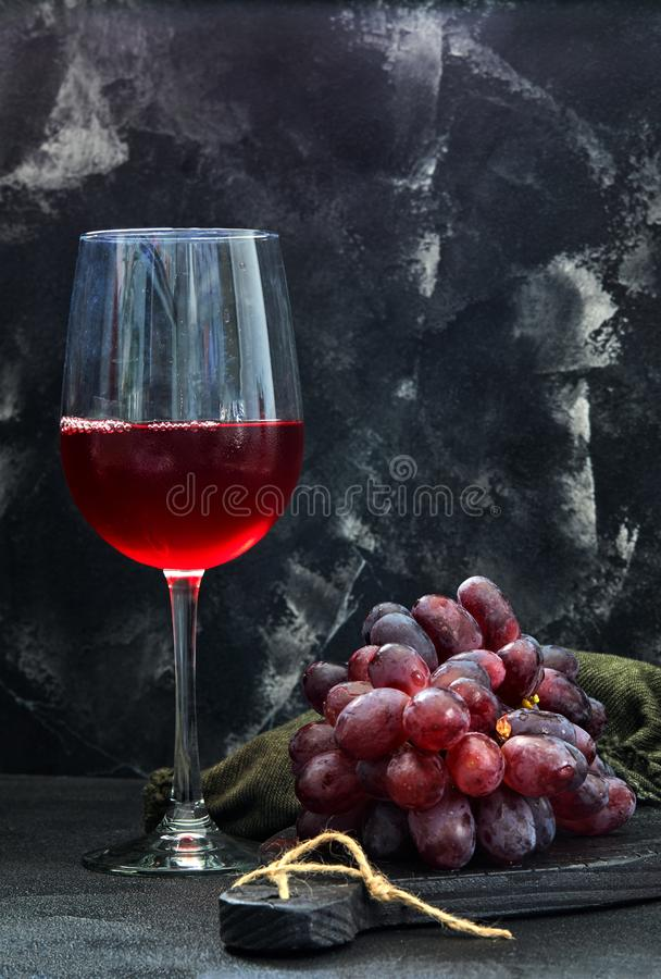 Glass of wine with grapes on a black wooden stand royalty free stock image