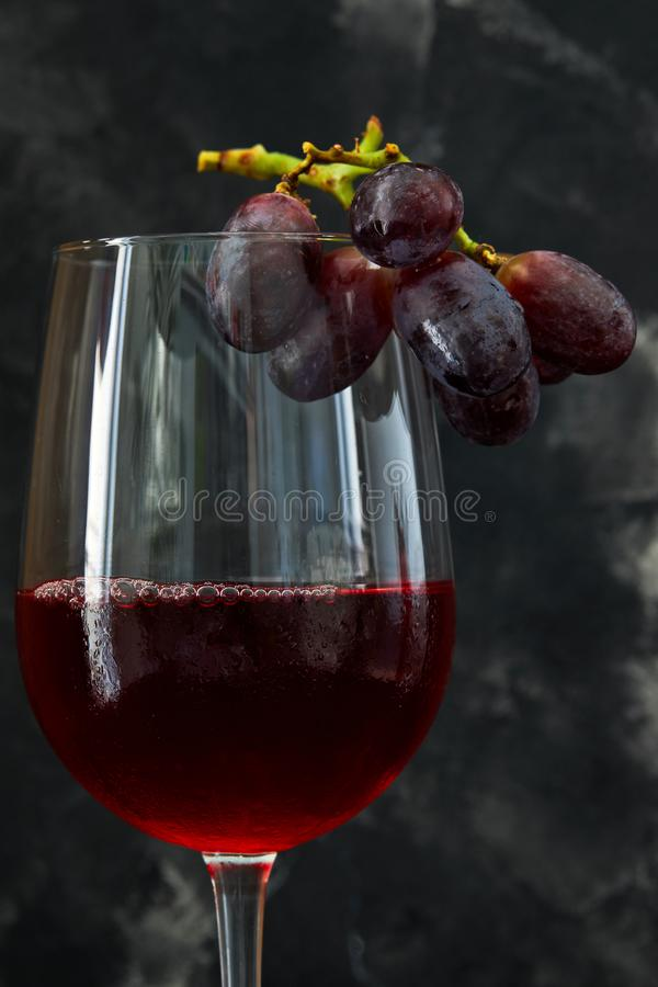 A glass of wine with grapes on a dark background stock image