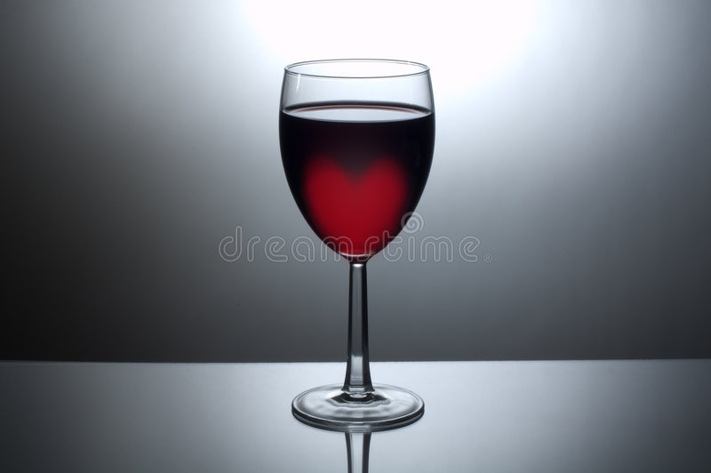 Glass of wine with heart shaped glow royalty free stock image