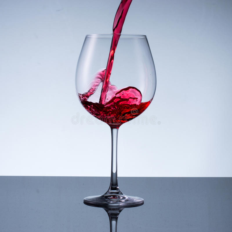 Glass of wine on a light background. Pouring wine in glass on a light background royalty free stock photography