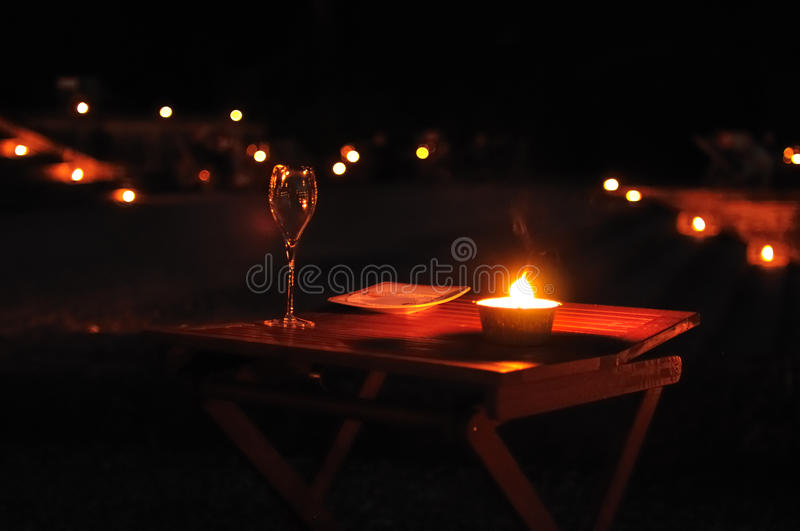 Glass of wine on an outdoor table. Single glass of wine with a candle on an outdoor table by night stock photo