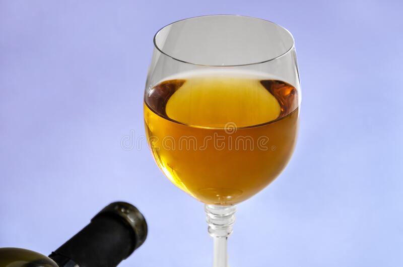 A glass of wine and a part of the bottle. Close-up. A glass of wine and a part of the bottle stock images