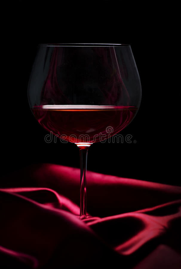 Glass of wine on red silk stock image