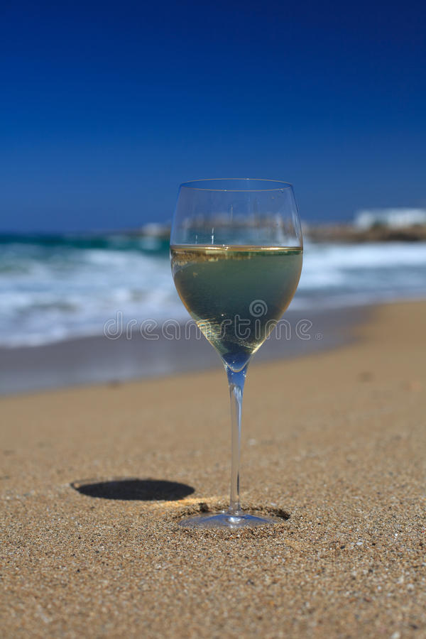 Glass of wine on the sand on the beach against a blue sky. A glass of white wine on the sand on the beach against a blue sky close-up. vertical royalty free stock photo