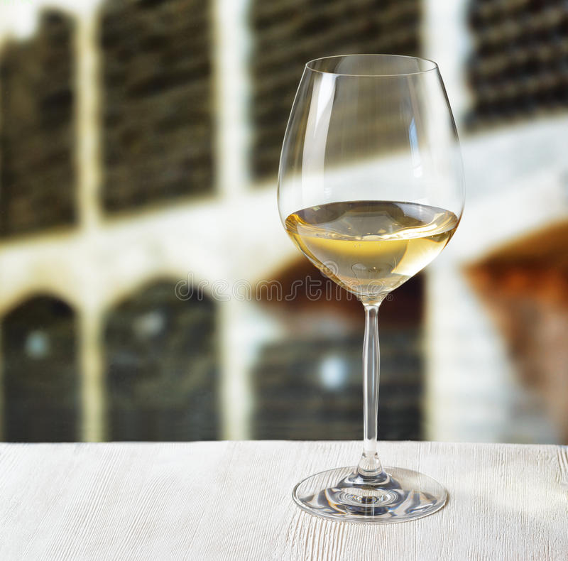 Glass of wine and wooden barrels in winery stock photo