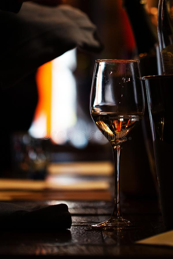 A Glass of wine on the wooden table. Of the restaurant stock images