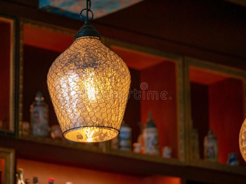 Glass and wire lamp cover on a hanging light bulb in dark bar. Glass and wire lamp cover on a hanging light bulb in a dark bar stock photography
