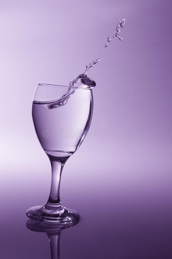 Free Glass With Clear Water Falling Over To Spill With Purple Back Li Royalty Free Stock Photo - 44869665