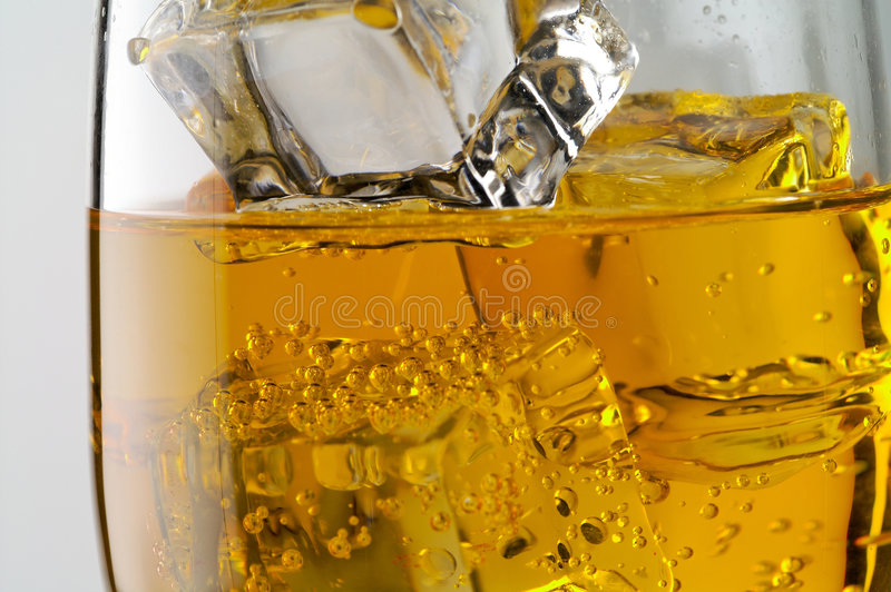 Glass of yellow drink with ice stock photo