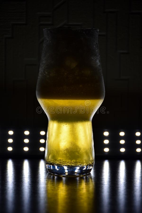 Glass with yellow liquid on a black background, a backlit glass, a luminous glass, beer in a glass royalty free stock photos