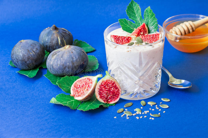 Glass of yogurt with fig fruit slices and honey. royalty free stock photography