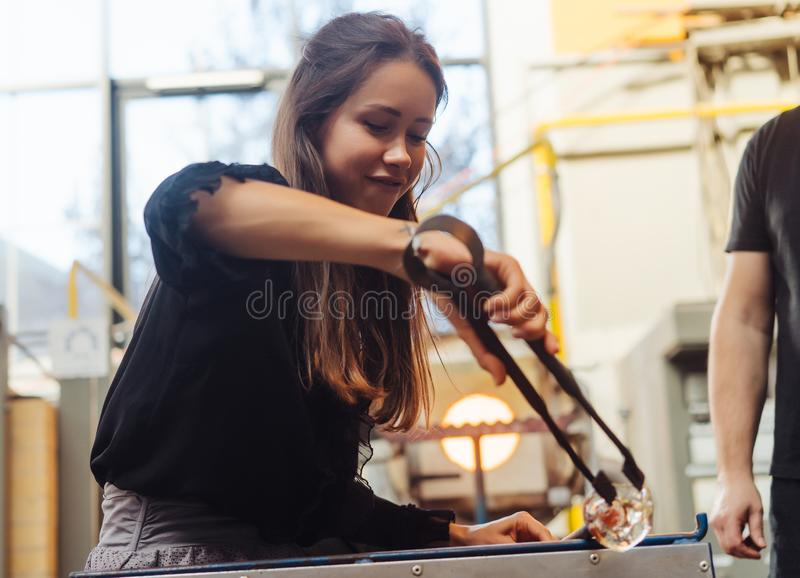A glassblower student tries to make a flower out of glass stock photo