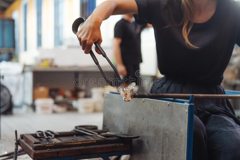 A glassblower student tries to make a flower out of glass. In the workshop stock photography