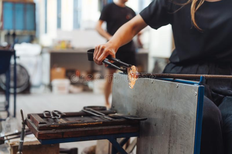 A glassblower student tries to make a flower out of glass. In the workshop royalty free stock photo