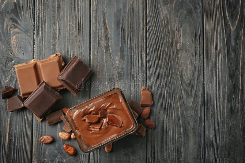 Glasschüssel mit flüssiger Schokolade auf Holztisch lizenzfreie stockbilder
