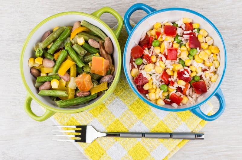 Glasschüssel zwei mit Gemüsemischung auf Tabelle und Gabel lizenzfreie stockfotografie