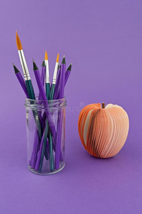 Glasschale mit Bleistiften und Bürsten auf violettem Hintergrund mit rotem gefälschtem Apfel lizenzfreie stockfotografie