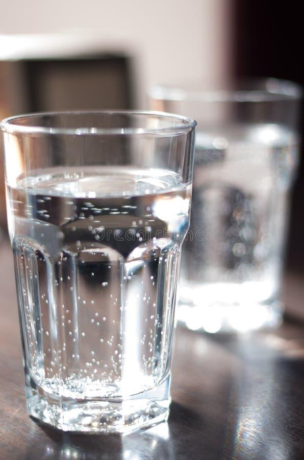 Glasschale mit Mineralwasser auf dem Tisch lizenzfreie stockbilder