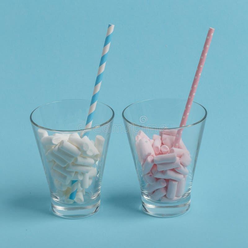 Glasschale mit Papierrohr und -eibischen auf einem blauen Hintergrund Minimalistic-Konzept stockbild