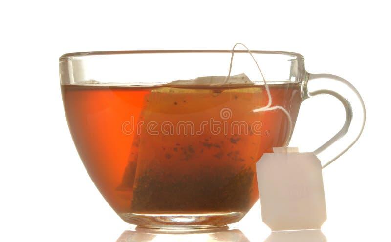 Glasschale mit Tee- und Teebeutelabschluß oben auf weißem lokalisiertem Hintergrund stockbild