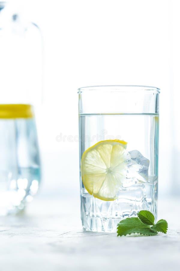 Glasschale und eine Karaffe des Wassers, des Eises, der Minze und der Zitrone auf einer weißen Tabelle lizenzfreies stockbild