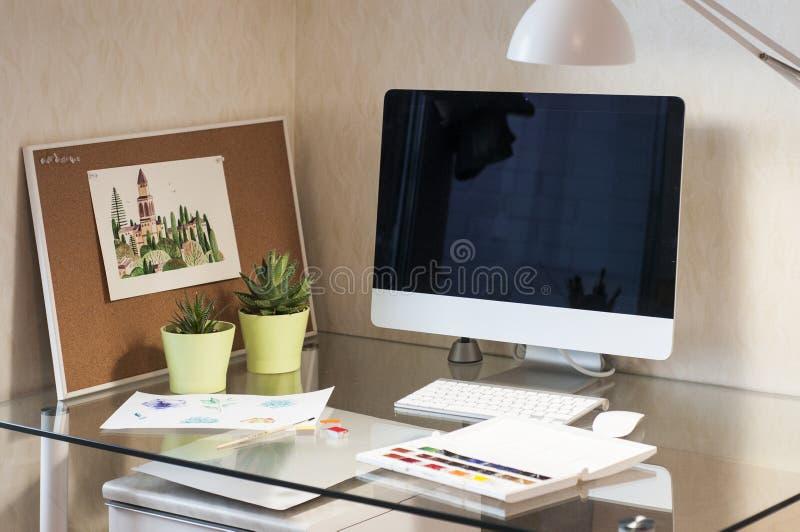 Glasschreibtisch mit Computer, Succulents in den grünen Töpfen, Lampe, Aquarellbild, Aquarellfarben und Korkenbrett stockbild
