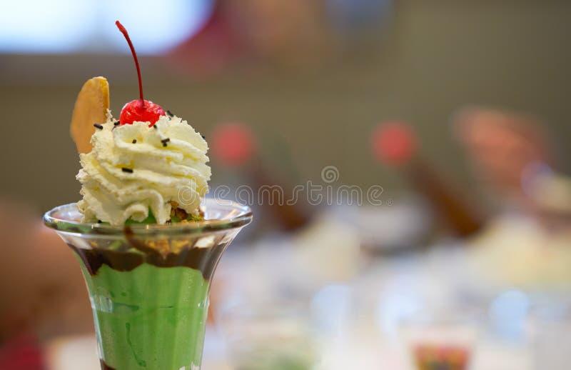 Glasscoupe med garneringglass i högväxt glass kopp med piskar kräm- det kotterånet royaltyfri fotografi