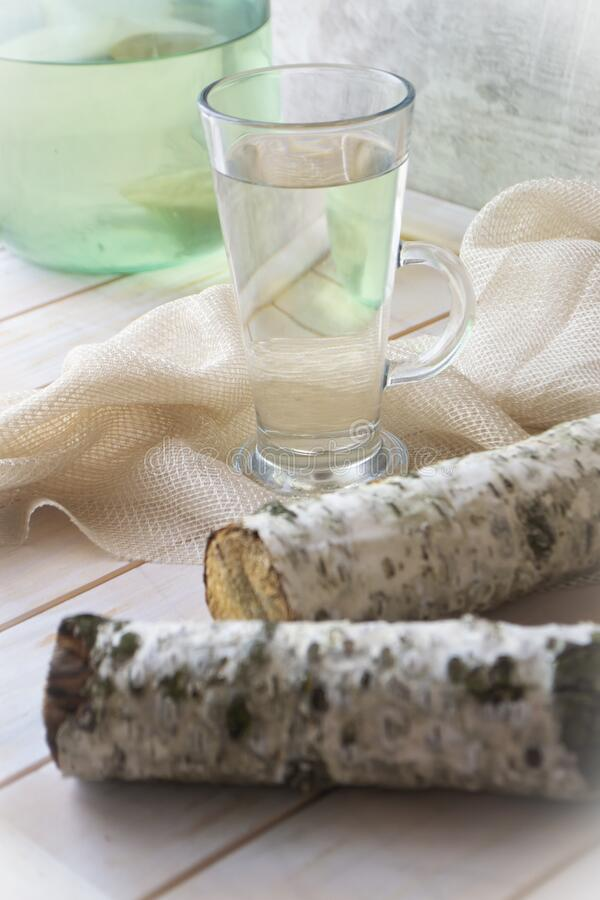 Glasse of birch sap on shabby wooden table with birch branch stock images