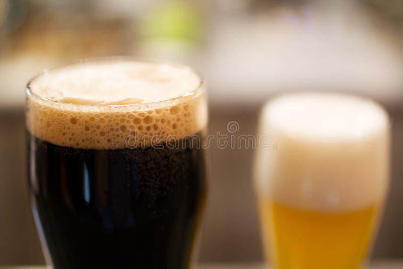 Glassed de la cerveza oscura y de la cerveza dorada fotografía de archivo