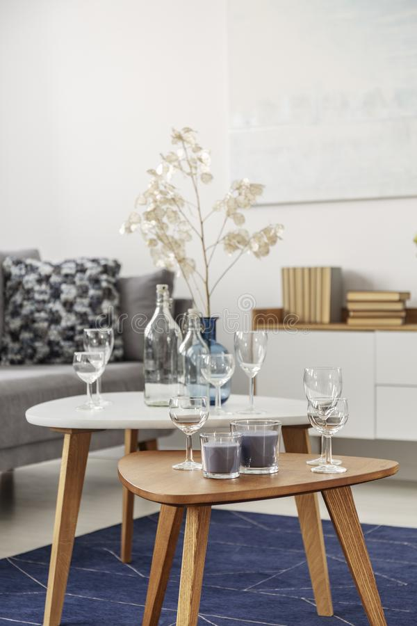 Free Glasses And Candles On Two Small Coffee Tables In Bright Living Room Interior Royalty Free Stock Photography - 146014737