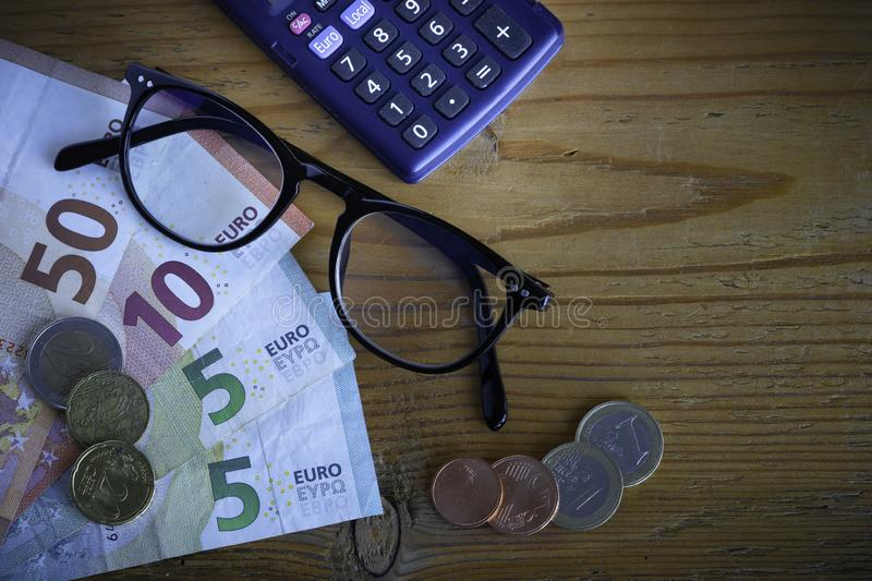 Glasses and banknotes in euros. Composition with banknotes and coins Euros, pair of glasses and calculator on wooden background royalty free stock images