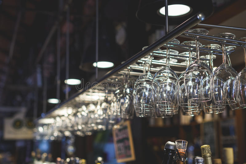 Glasses on a bar rack royalty free stock photography