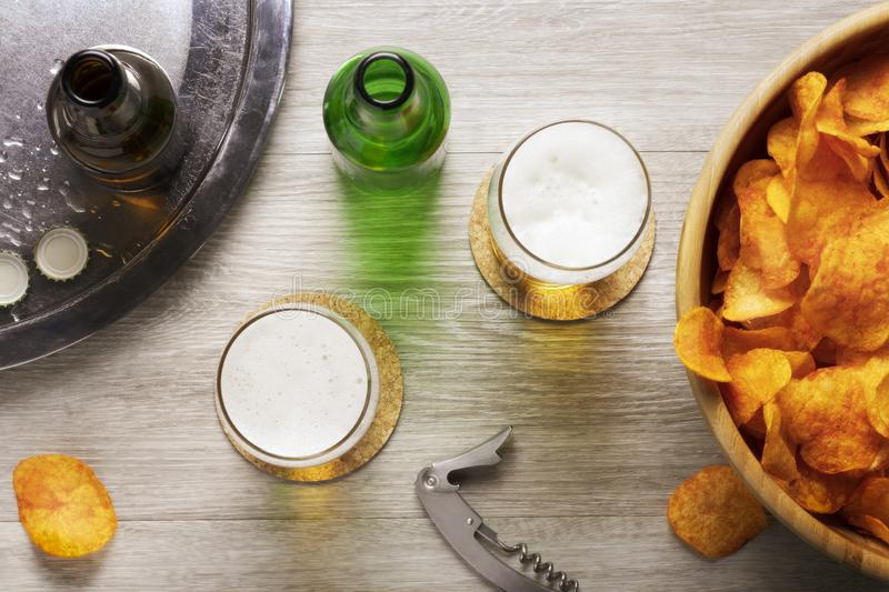 Glasses of beer, beer bottles and crisps and a bottle opener, top view, flat lay stock image