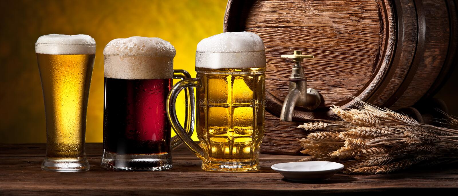Glasses of beer and beer cask on the wooden table. Craft brewery.  royalty free stock image