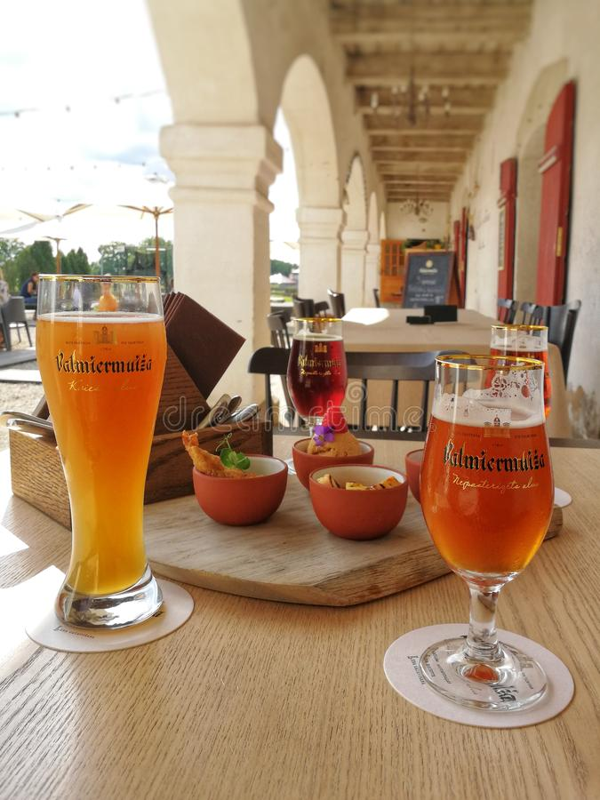 Glasses of beer and snacks on the table in the local restaurant near to the beer manufacture, Valmiera, Latvia. Glasses of beer and snacks on the table in the stock photo
