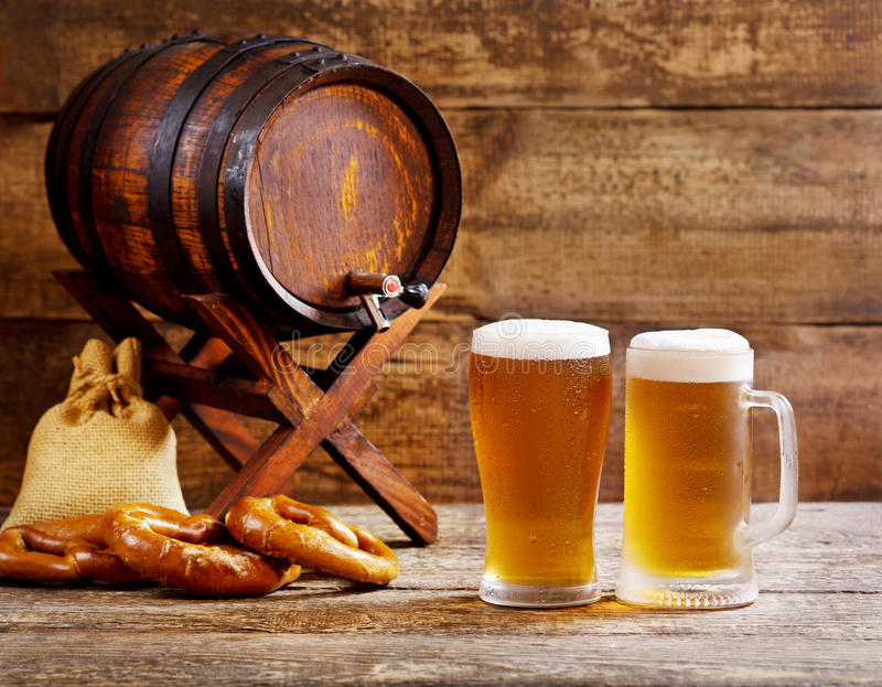 Glasses of beer with wooden barrel royalty free stock photos