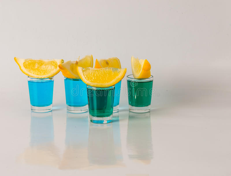 Glasses with blue and green kamikaze, glamorous drink, mixed drink poured into shot glasses. Party set stock photo