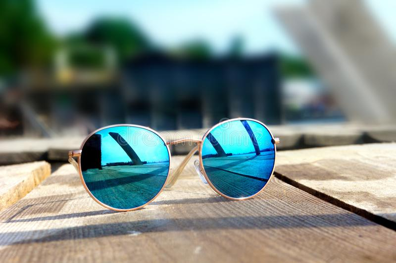 Glasses with blue glasses on the sun lie on a wooden floor rest royalty free stock photo