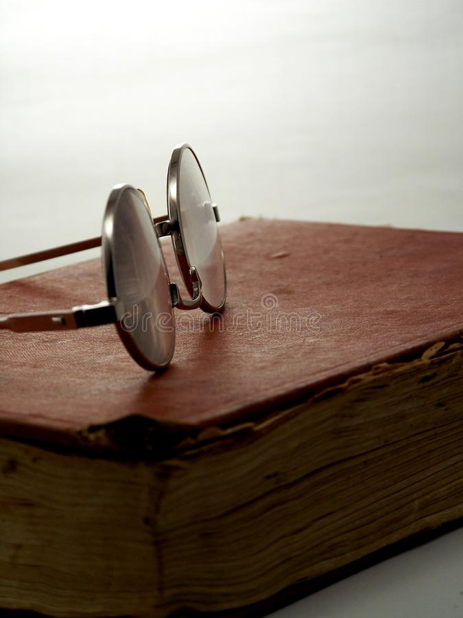 Glasses on book. stock photos