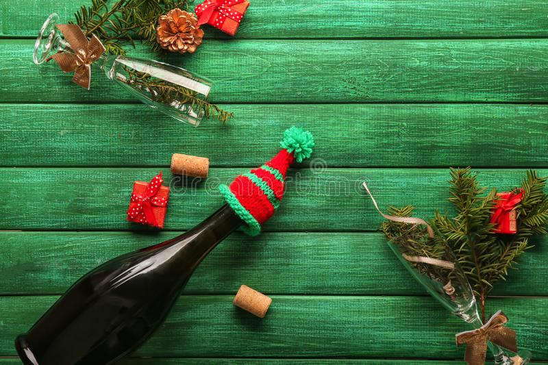 Glasses and bottle of champagne with Christmas decor on color wooden background royalty free stock photo