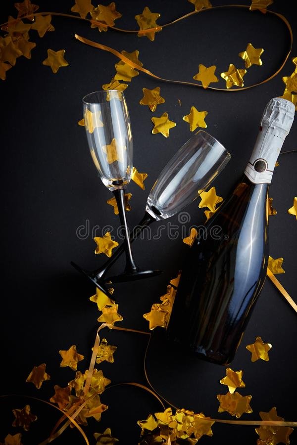 Glasses and bottle of champagne with golden serpentines and confetti royalty free stock photos