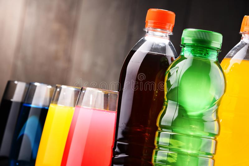 Glasses and bottles of assorted carbonated soft drinks. In variety of colors royalty free stock photography
