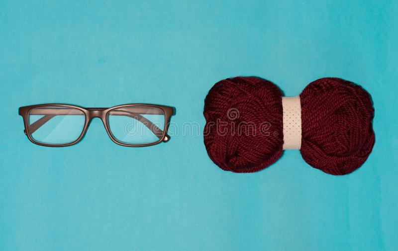 Glasses and bow close lie on a blue background royalty free stock images