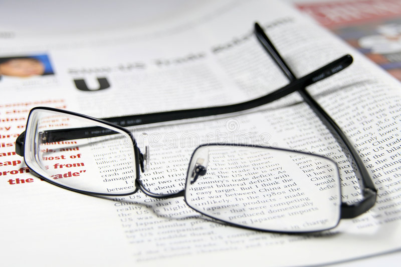 Glasses and business magazine royalty free stock image