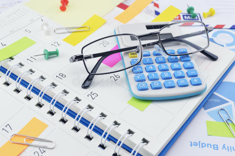 Glasses, calculator, pin and colorful sticky notes on business d royalty free stock photography