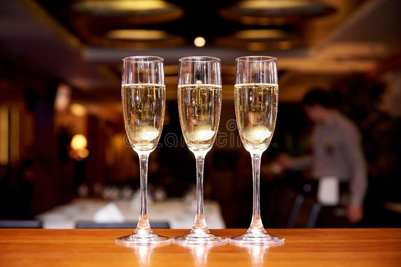 Glasses with champagne on the bar counter in a restaurant against a dark background royalty free stock photo